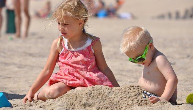 Meisje speelt met zand op het strand van Katwijk Zuid-Holland in de zomer